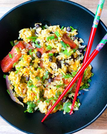 egg fried rice with garden vegetables in a black shallow bowl