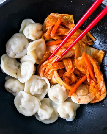 spicy red kimchi in a bowl with chopsticks